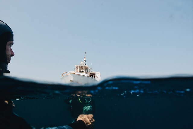 Over under shot of a man scuba diving near a boat