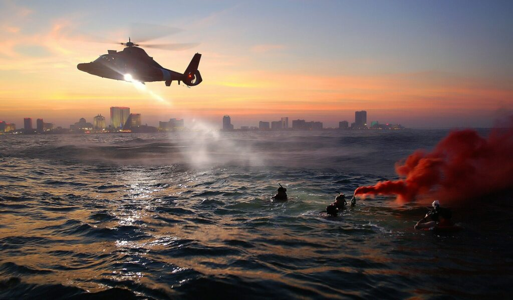 Helicopter rescues people at sea with smoke flare deployed