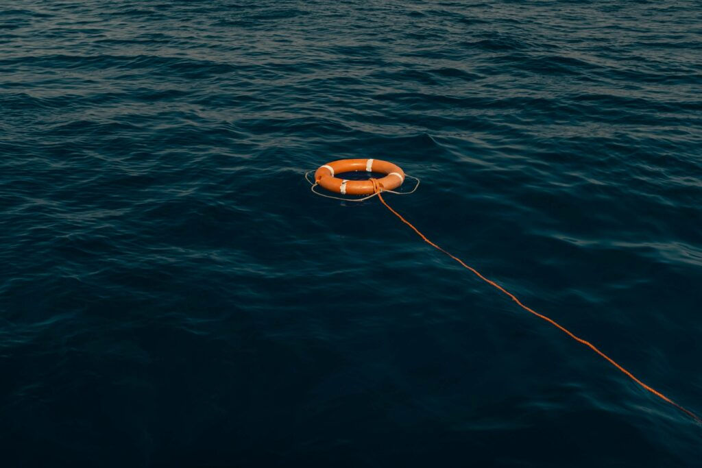 Orange life buoy on a rope in the ocean