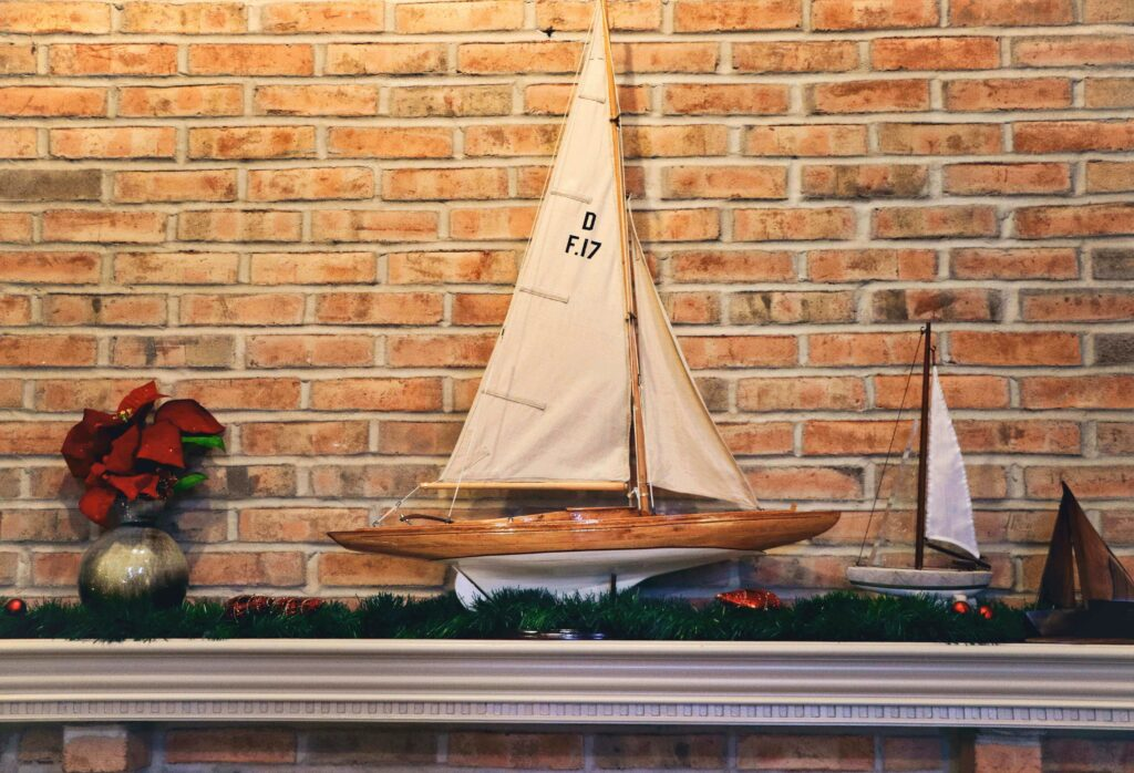 Christmas boat decorations on fireplace shelf