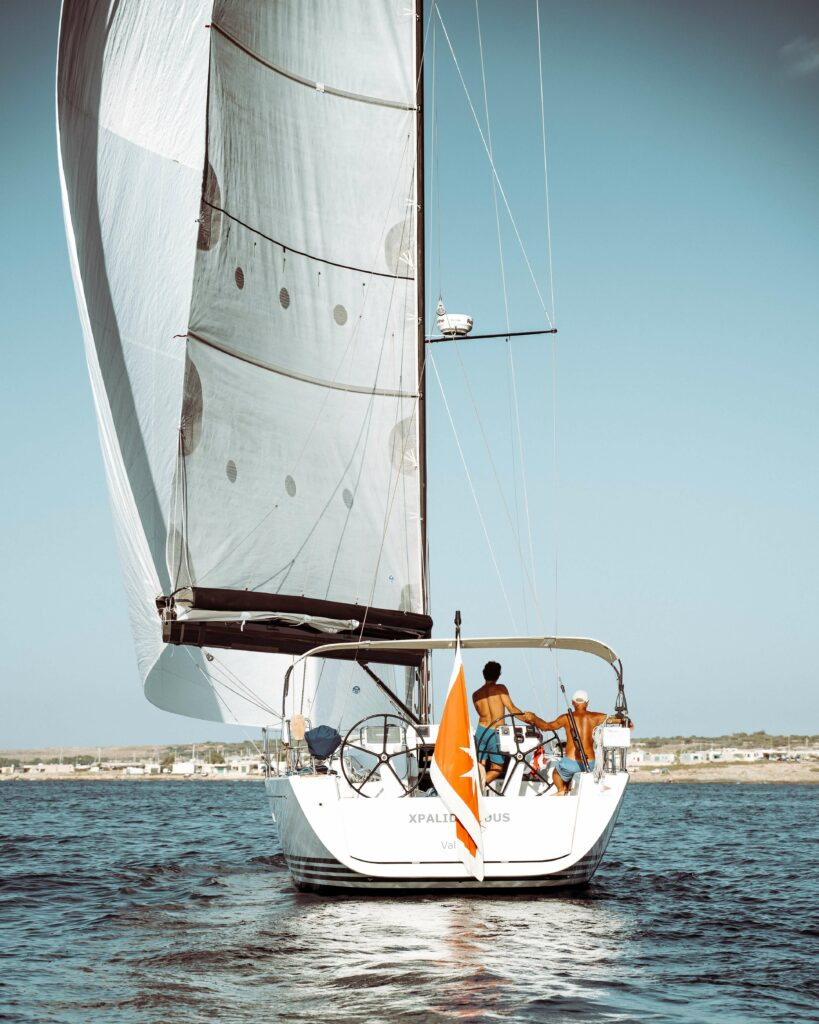 Two people hanging out on a sailboat in the ocean