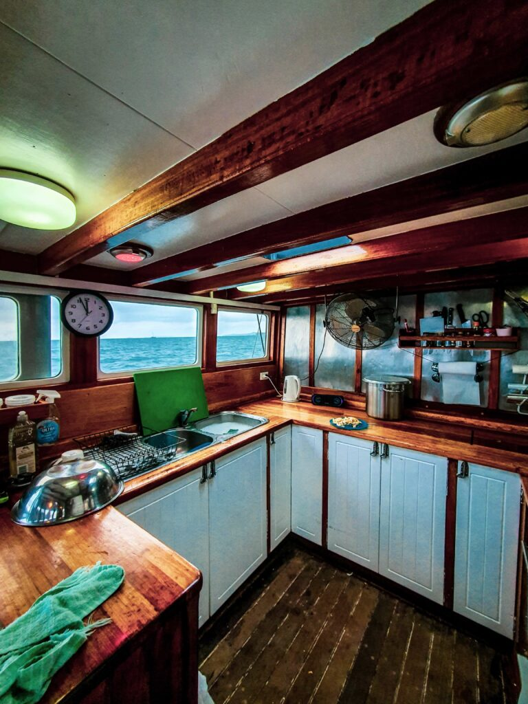 Boat galley with wooden countertops and white cabinets