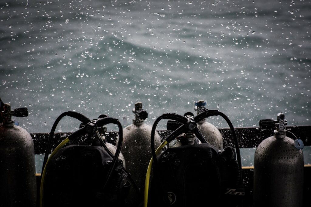 Scuba gear set up with tanks on a dive boat in the rain
