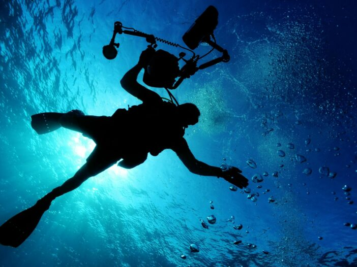 Silhouette of scuba diver with photography equipment