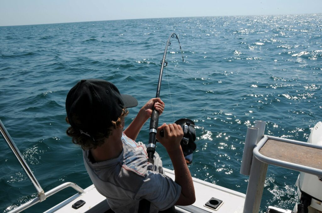 Man reeling in a fish on a boat in the ocean