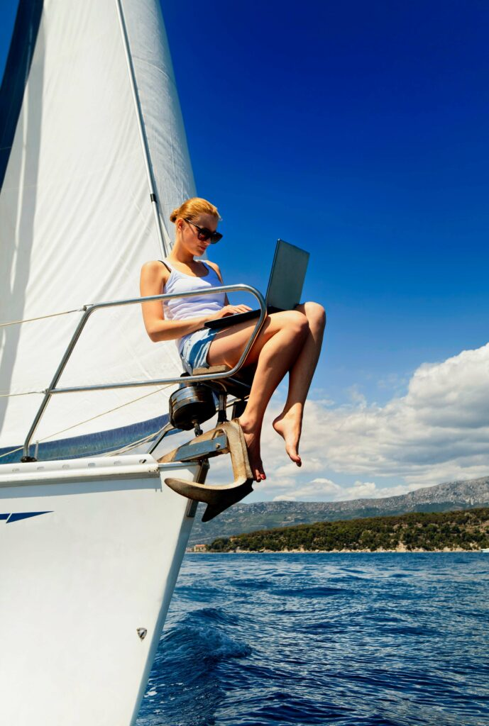 Woman works on her laptop while sitting at the bow of a sailboat