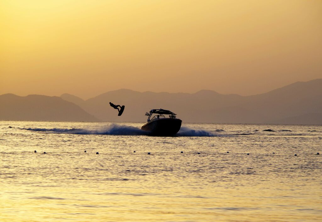 Person jumping a wakeboard behind motorboat at sunset