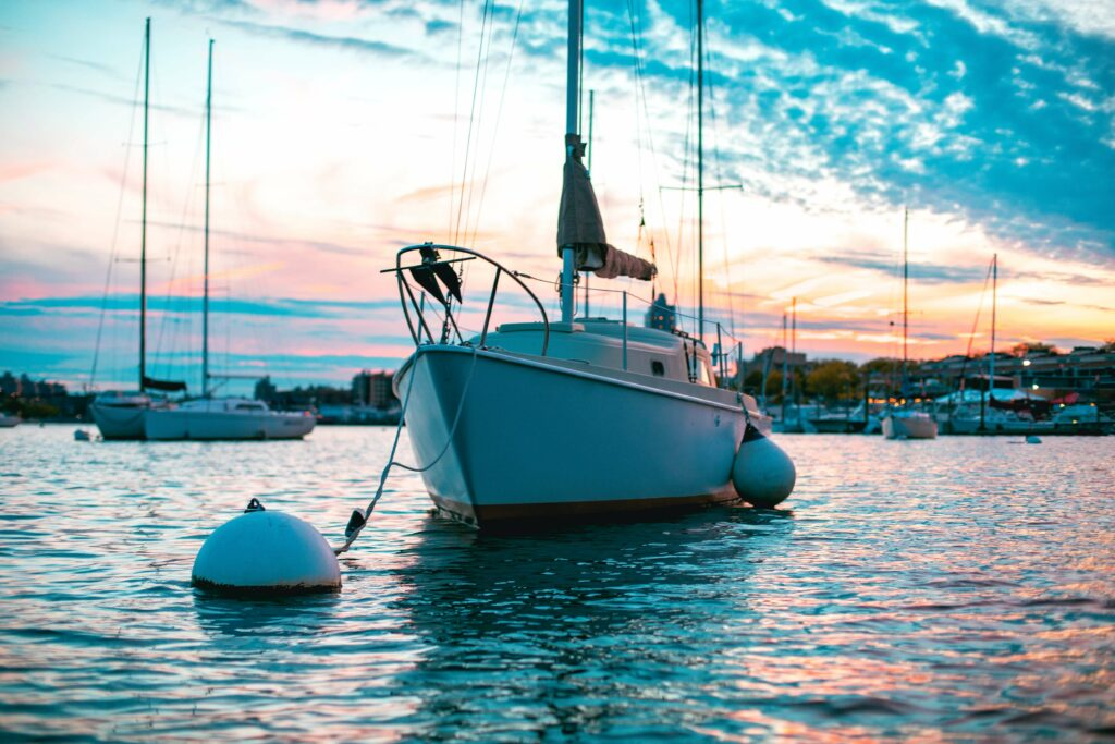 White sailboat on a mooring line near the pier at sunset