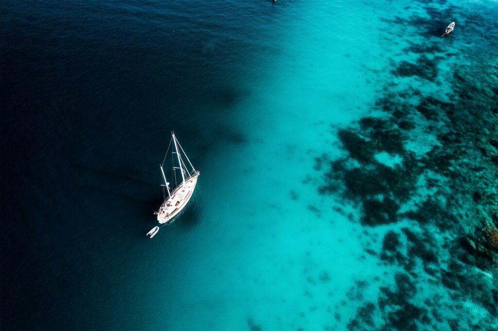 Aerial view of a sailboat on turquoise blue water in Thailand