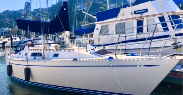 White Nordic 40 sailboat with blue sails in a marina