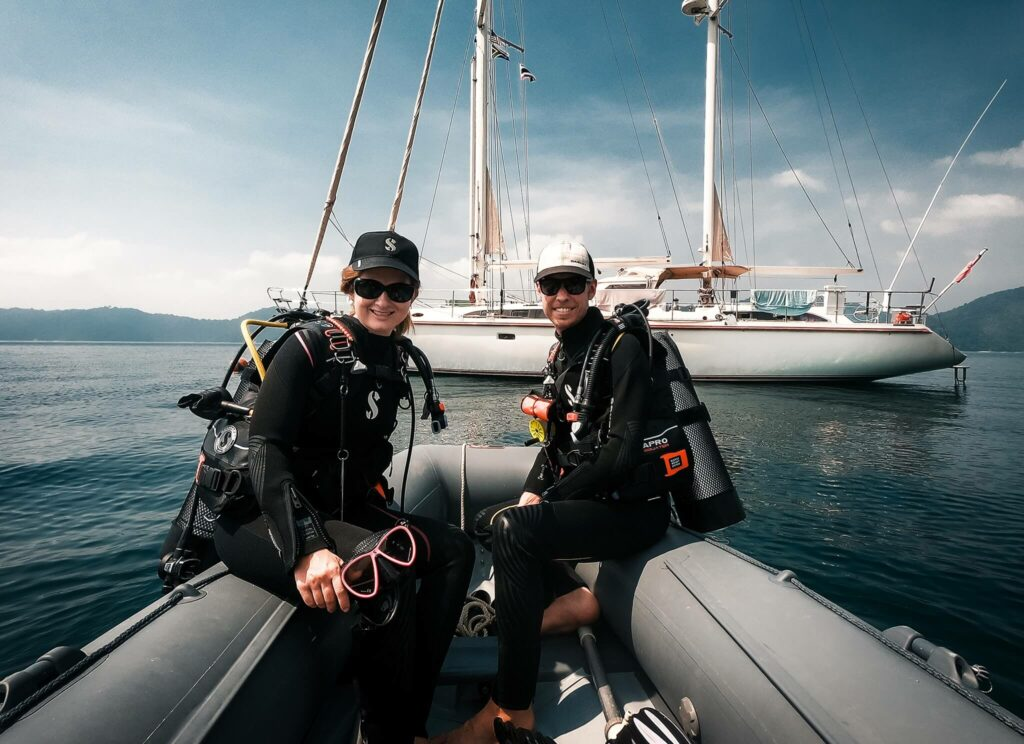 Couple scuba diving from their dinghy in Thailand