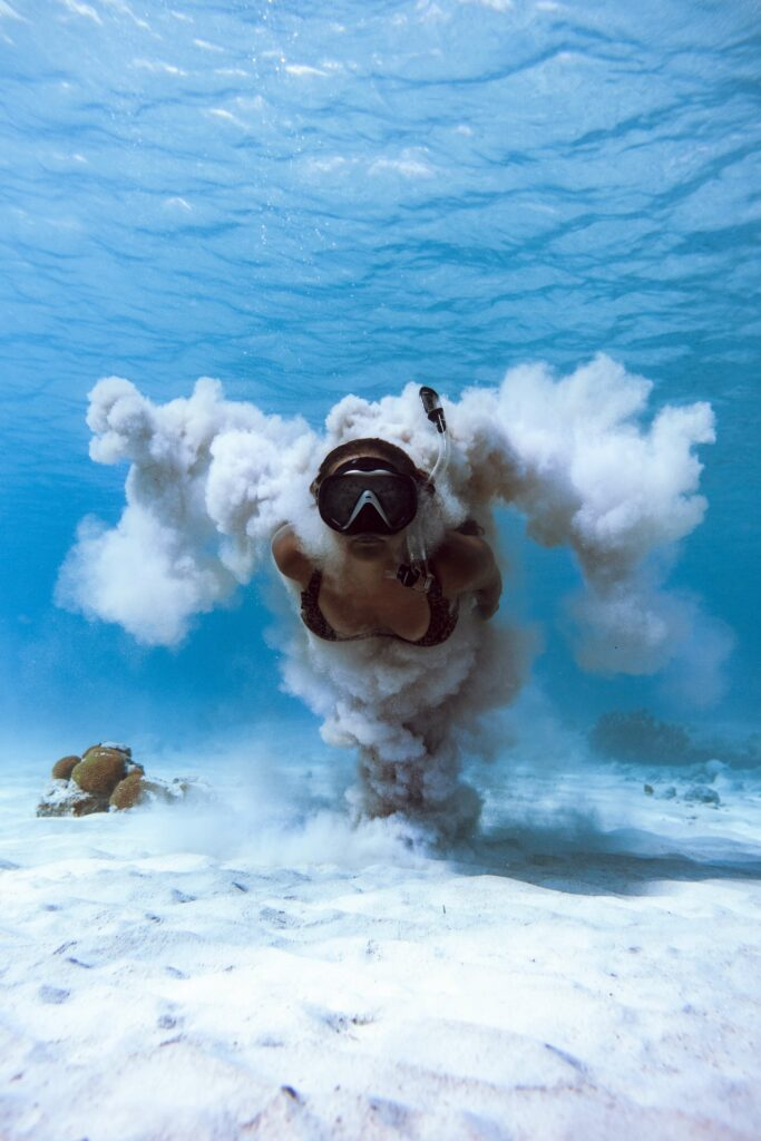 Woman freediving with a diving mask and snorkel along the sand