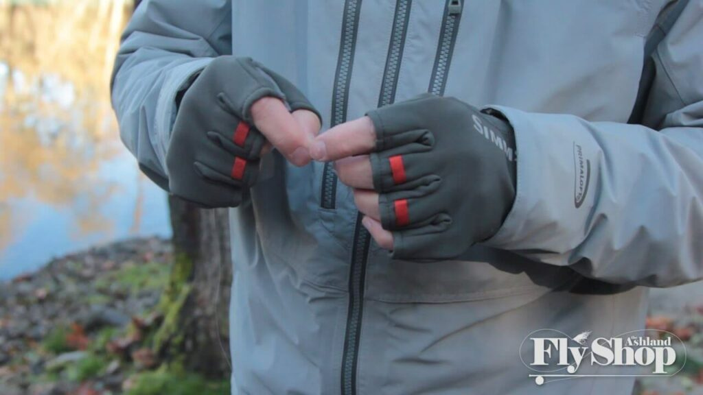 Person wearing Simms fingerless gloves tying a fishing line