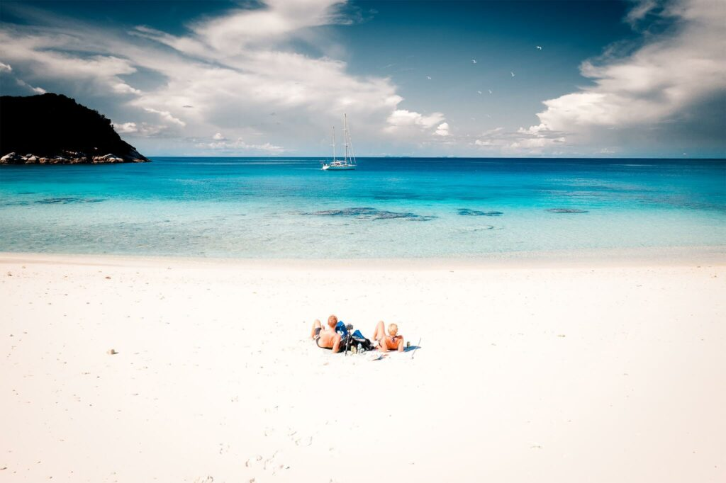 Chris and Jennifer Likins lay on a deserted white sand beach in Thailand