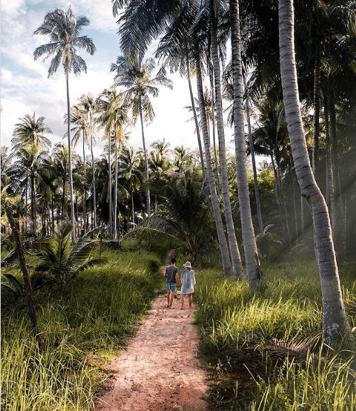 Jennifer and Chris Likins walking down a dirt path near palm trees in Thailand