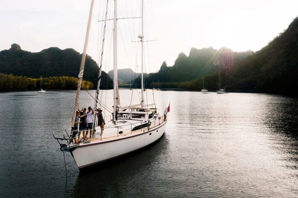 Friends standing at the bow of a sailboat in Thailand