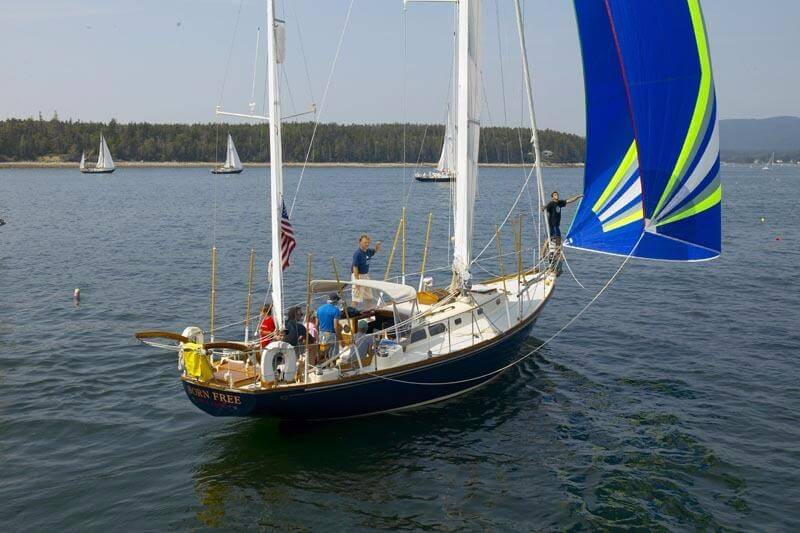 Group of people on a Hinckley Bermuda 40 with blue sails