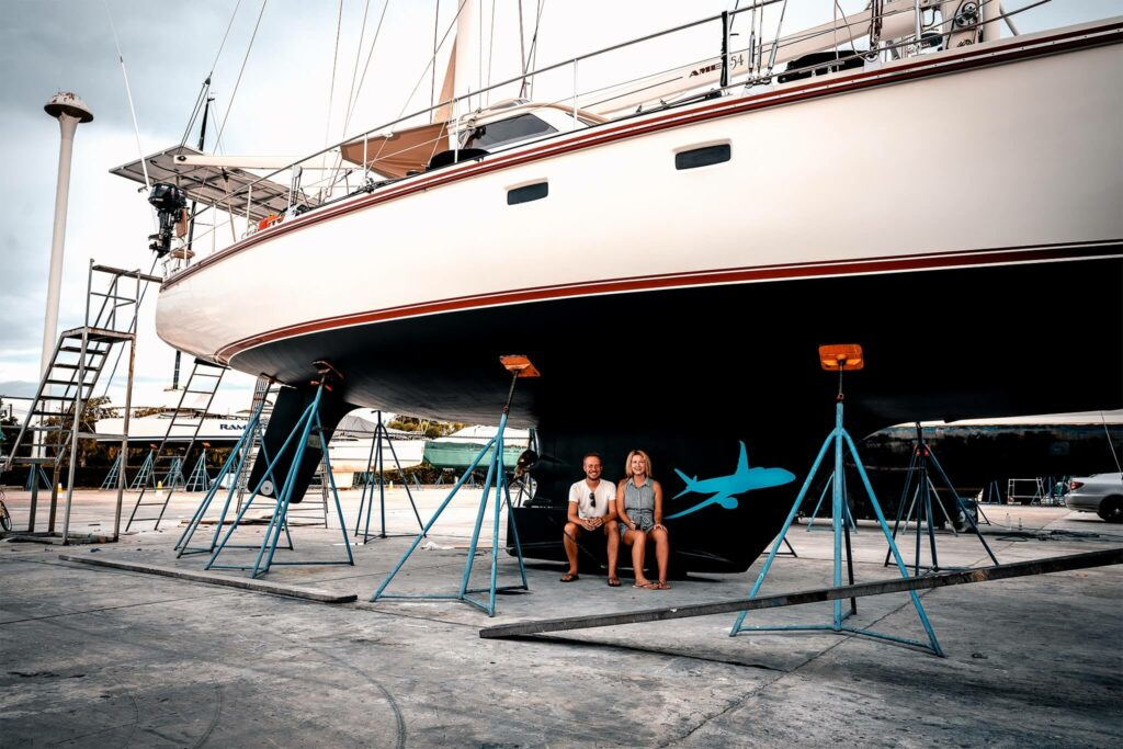 Couple sit in front of their sailboat during an overhaul
