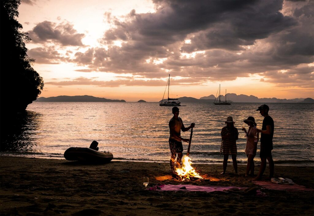 Bonfire with friends on the beach at sunset in Thailand