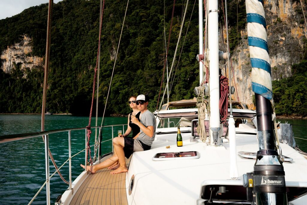 Jennifer Likins and Chris Likins drinking champaign on their sailboat in Thailand