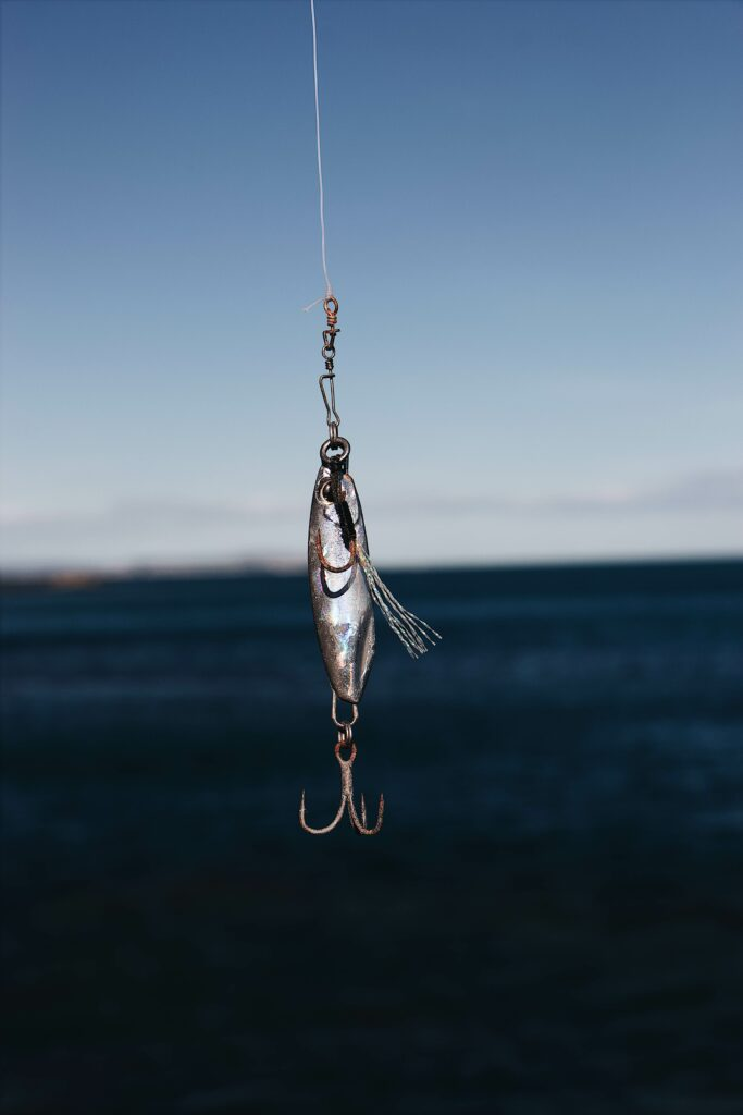 Silver spinning lure hangs on a fishing line