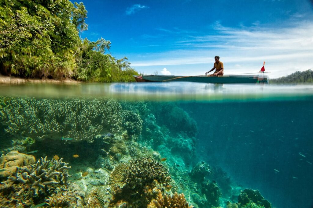 Man fishing over a coral reef in a canoe