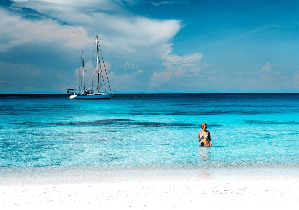 Jennifer Likins in the clear blue waters of Thailand with her sailboat in the background