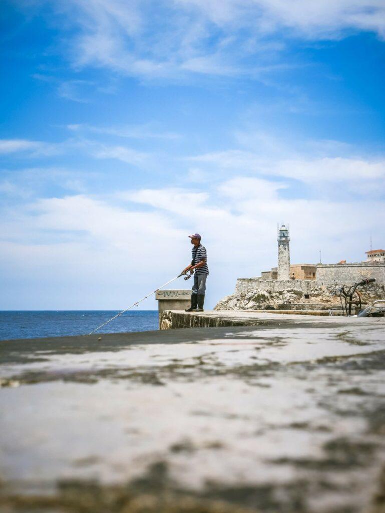 A man shore fishing from a concrete platform in Cuba