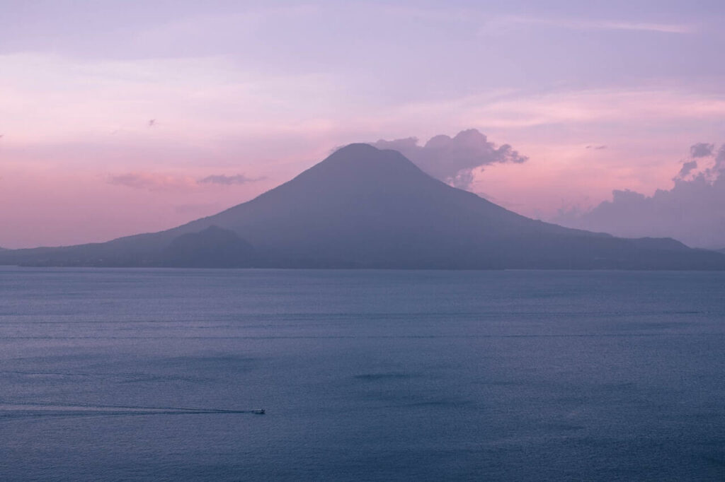 Pink and purple ocean sunset with a volcanic backdrop in Guatemala