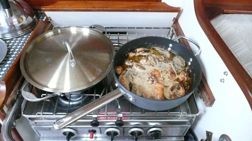 Cooking seafood on a stovetop in a boat galley
