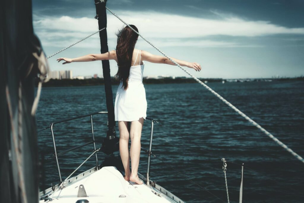Woman stands at the front of a sailboat with her arms stretched out