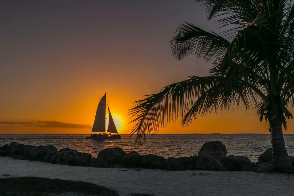 View of a sailboat in front of a sunset from shore