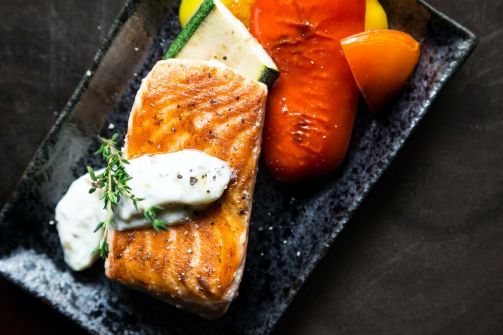 Grilled salmon with tartar and dill alongside vegetables
