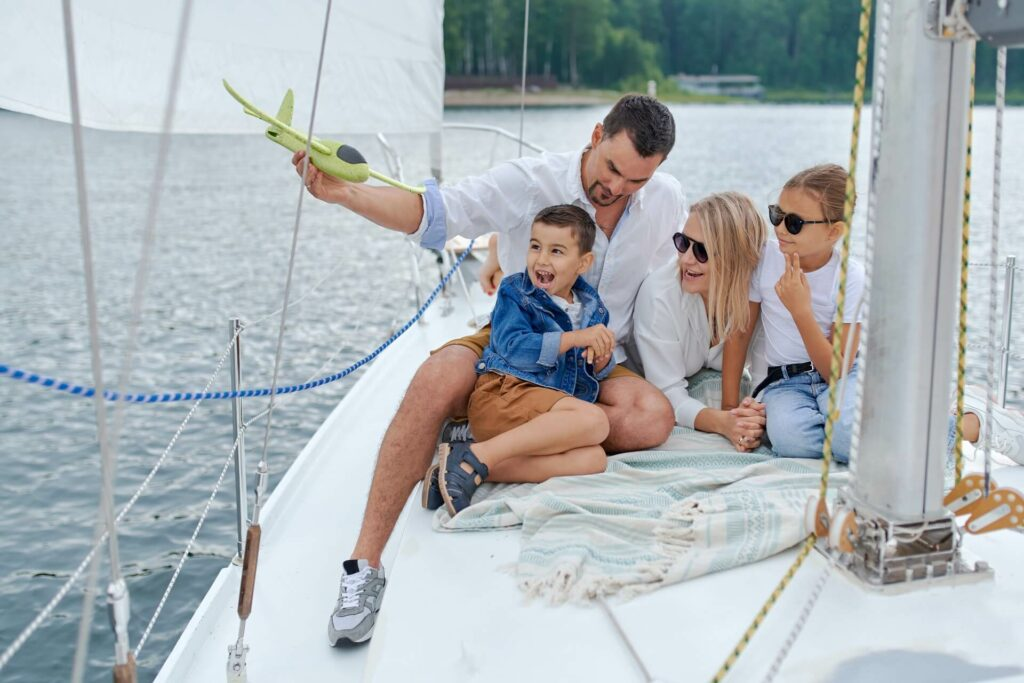 Family interacting on the bow of a sailboat