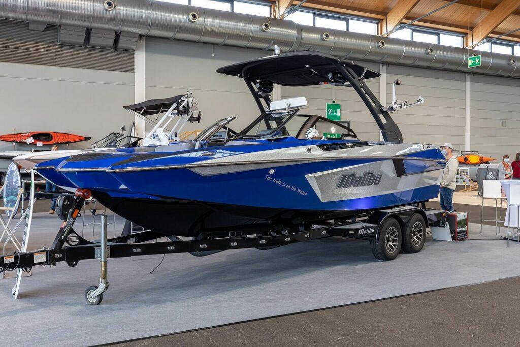 Blue Malibu speedboat on a trailer inside of a garage