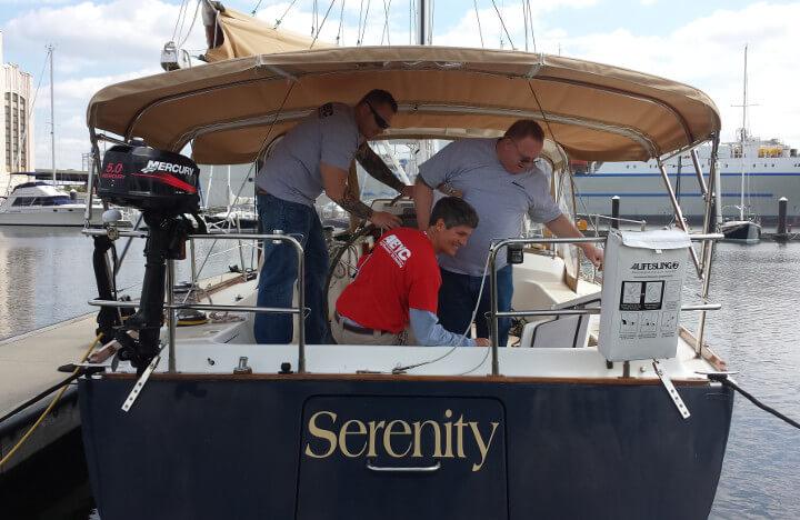 Three men conducting a boat survey on a sailboat