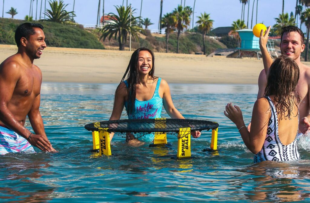 Group plays water games near the beach on a sailing trip