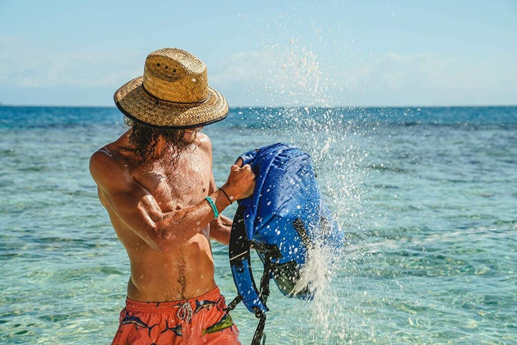 Man shakes water off of the Skog A Kust Backsak Pro Daybag in the ocean