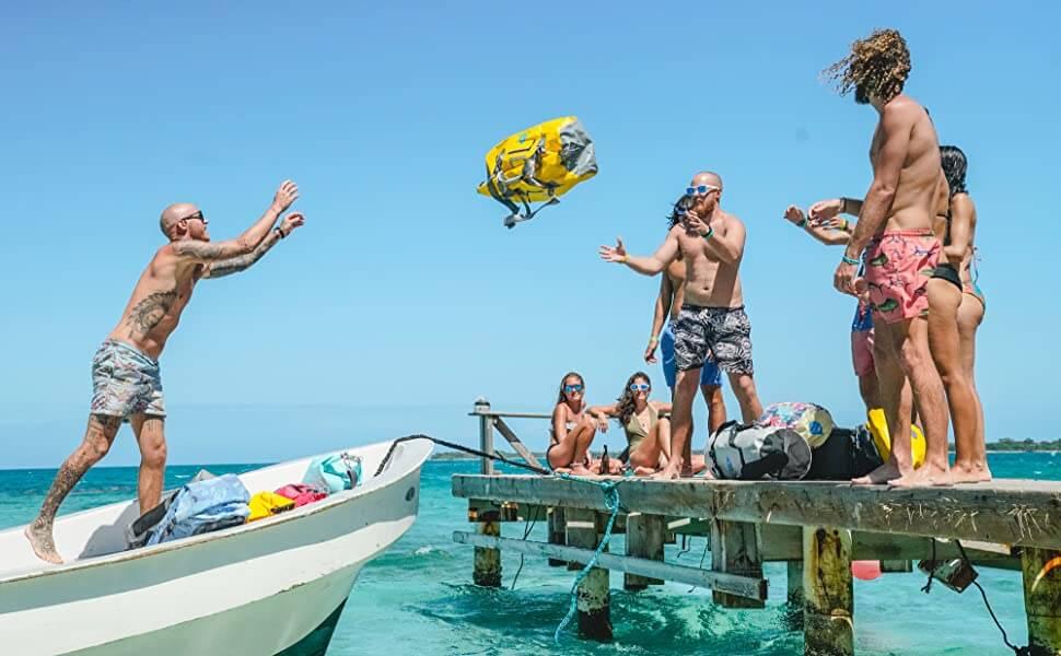 Man throws a yellow Skog A Kust Duffel bag from a boat