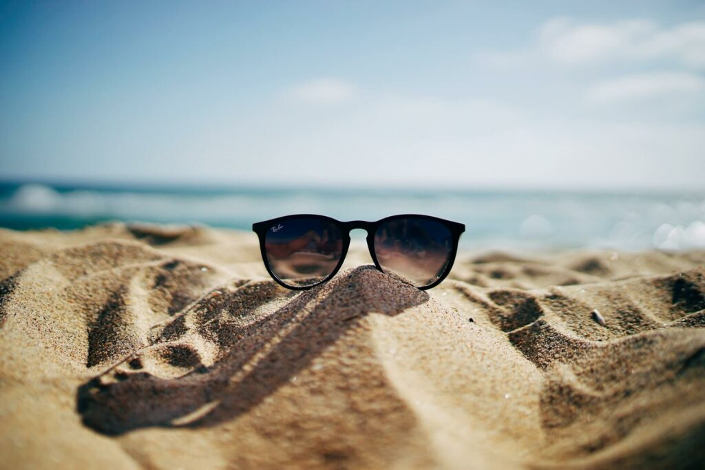 Pair of sunglasses in the sand on a sailing vacation