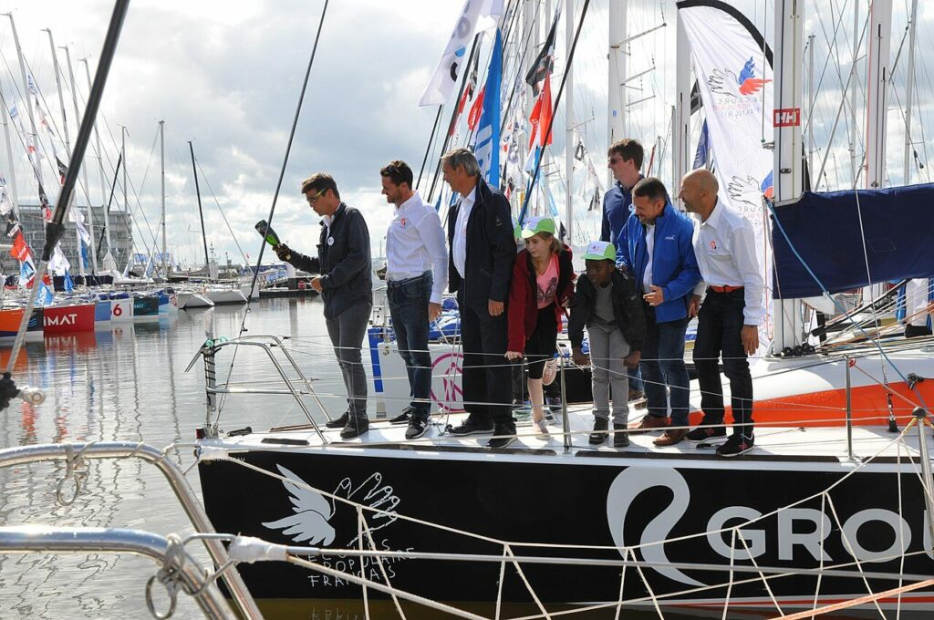 A group of people gather at a boat christening ceremony as the owner prepares to break a bottle of champagne over the bow of the boat