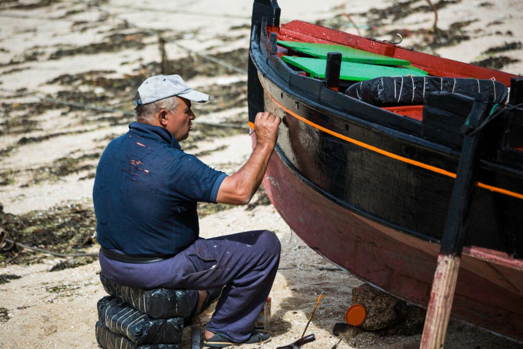 a man paints the new name of a boat on the hull during an overhaul