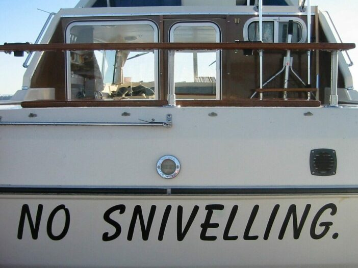 """the name """"No Sniveling"""" painted at the bow of a white sailboat with dark brown woodwork"""
