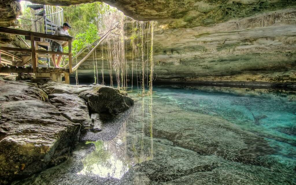 A man stands over a pool of water inside of a cave at Inagua National park in the Bahamas