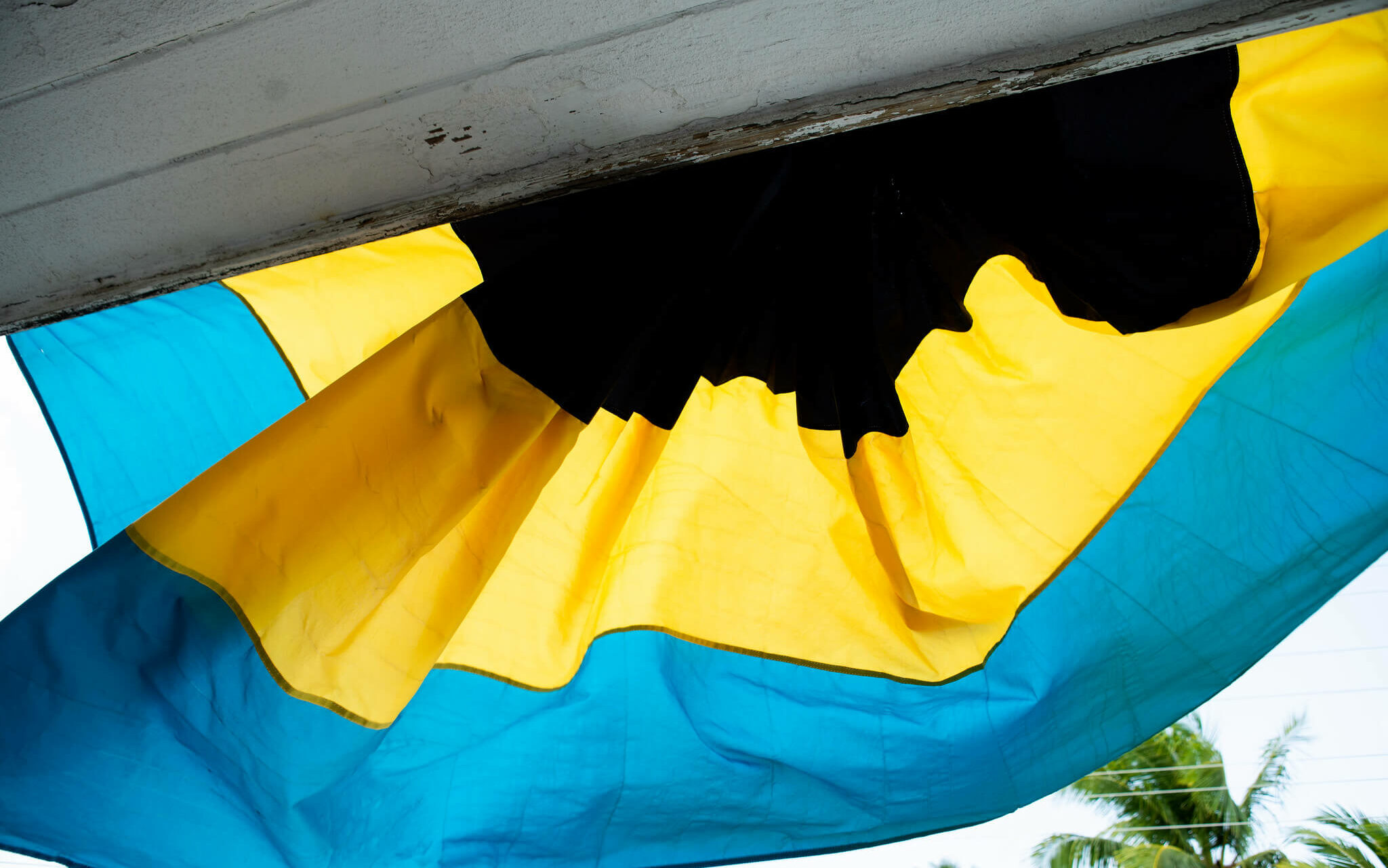 The Bahamas country flag hanging from a front porch in front of palm trees