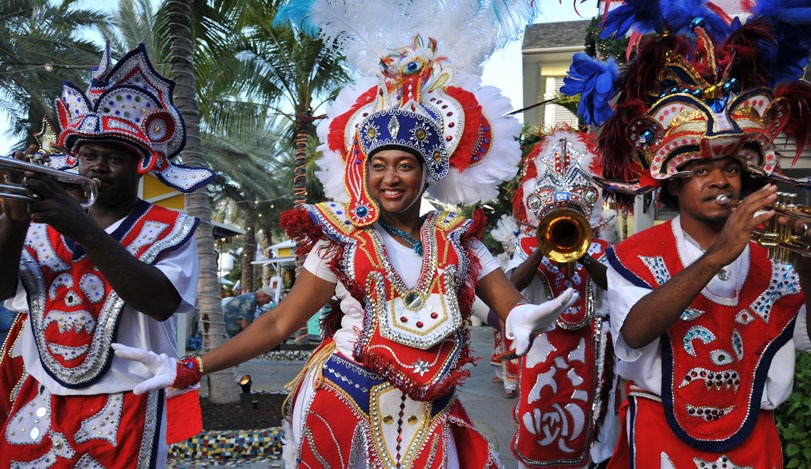 People dressed in colorful red, white, yellow, and blue costumes playing instruments and dancing for the Junkanoo Festival in Nassau, Bahamas