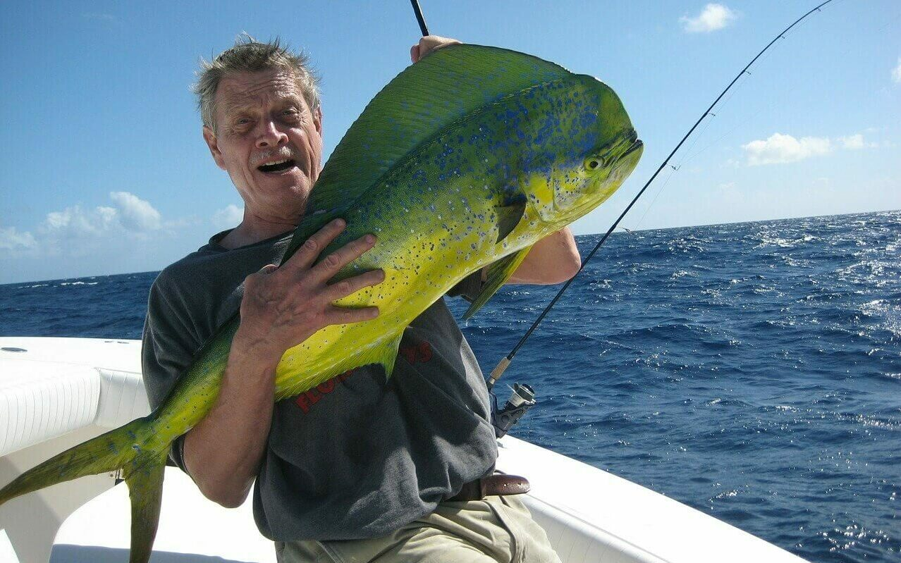 A man holds a large mahi-mahi that he just caught while fishing from a boat in the Bahamas