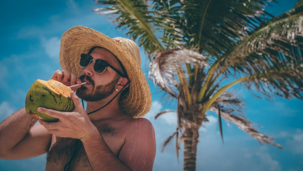 A man sips from a fresh coconut in a straw hat under a palm tree in Grand Bahama