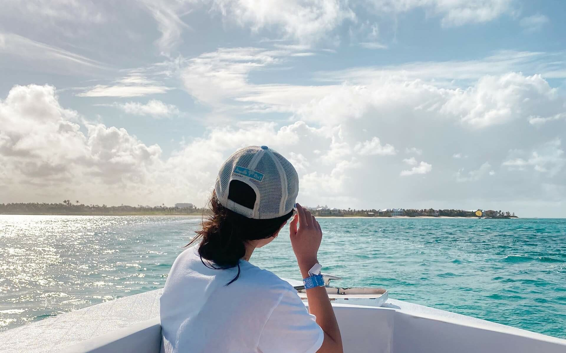 A woman in a hat looking at an island from a boat in the Bahamas