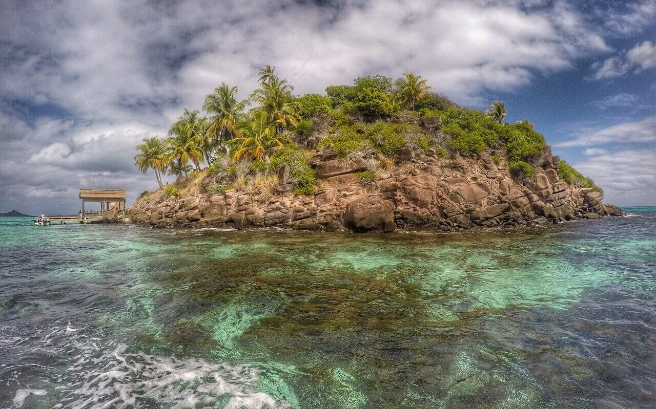 A small uninhabited island covered in rocks and palm trees in the Bahamas